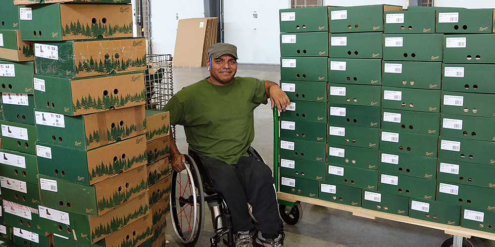 Milson Cruz pauses for a picture as he works on reverse logistics re-boxing for Danner boots.