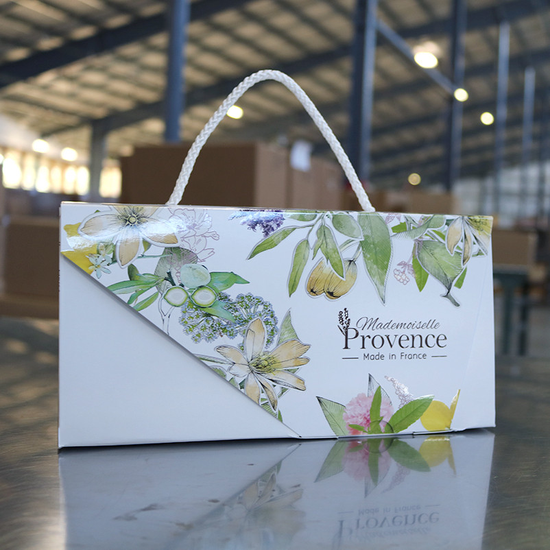 A decorative flower gift box from Mademoiselle Provence sits on a table waiting for shipment in a warehouse.