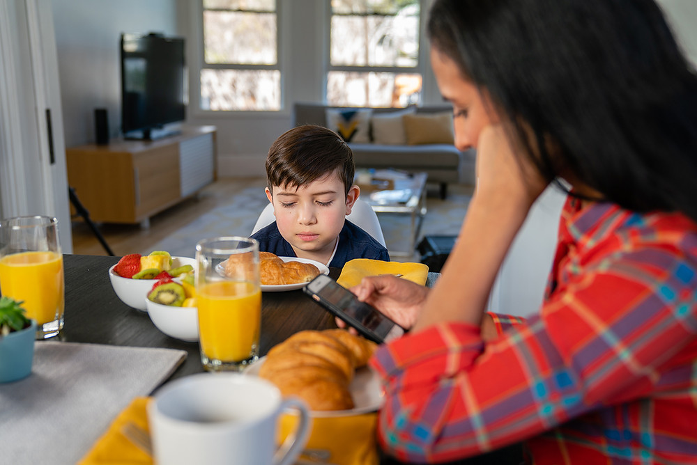 mother looking at phone over breakfast as son looks sadly at food