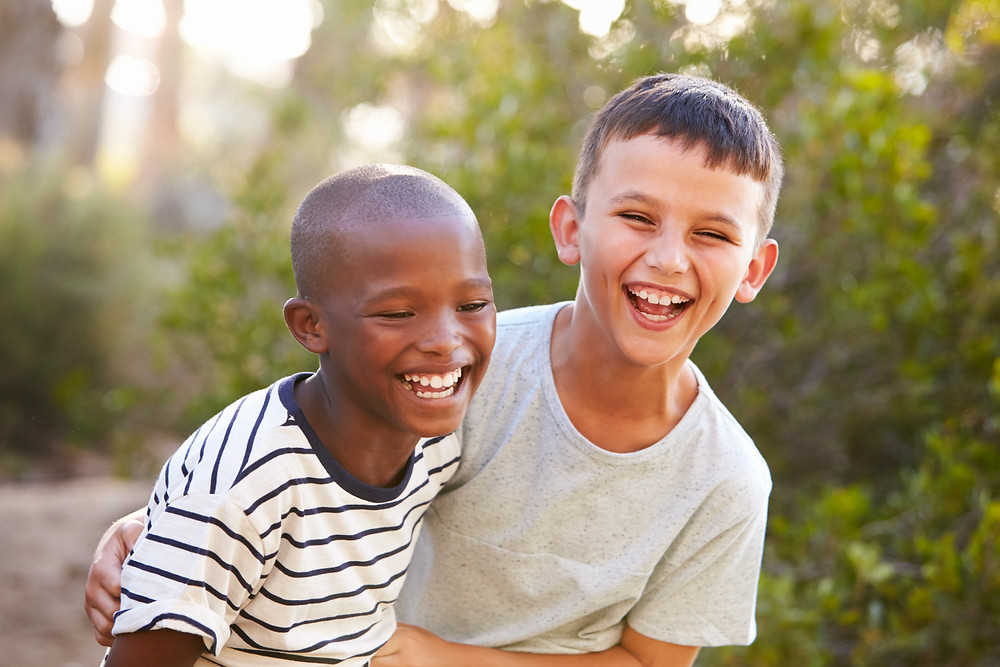 two boys of different race laughing together