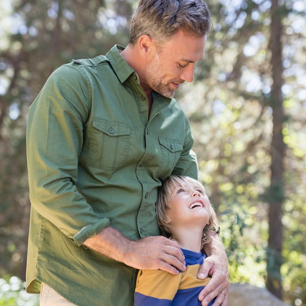 man smiling while holding and looking down at young son