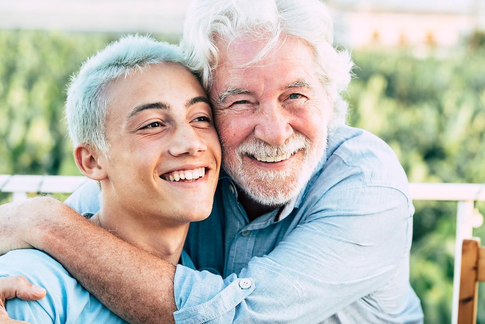 grandad hugs grandson while both smile. both have silver hair