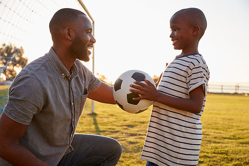 a-boy-holds-a-football-while-playing-wit