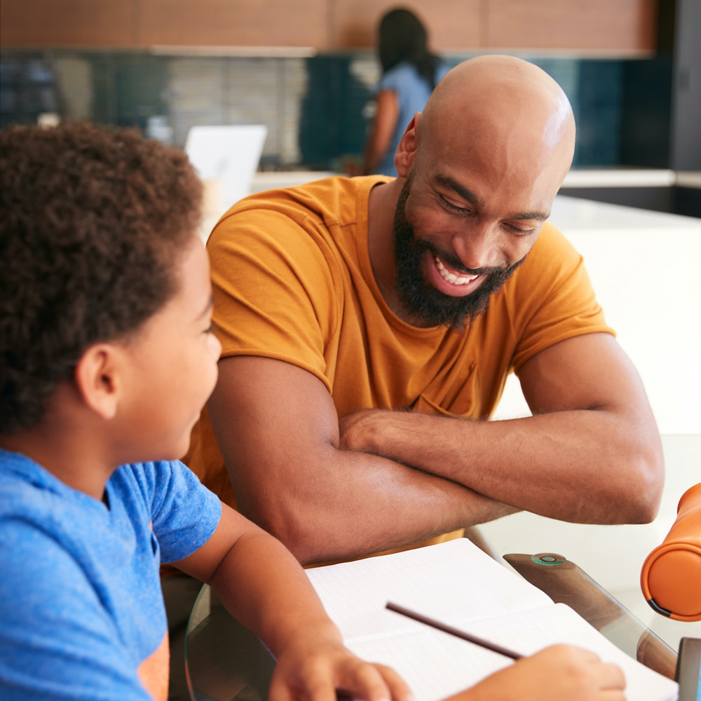 man smiling while helping young boy with homework