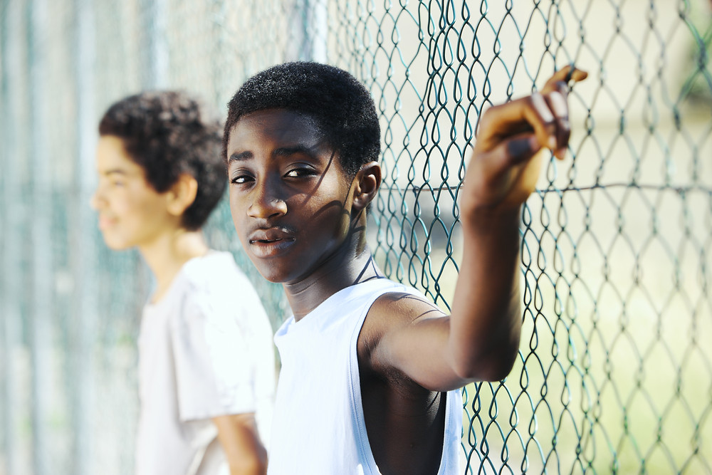 two boys relaxing while leaning on chainlink fence- one boy stares at camera