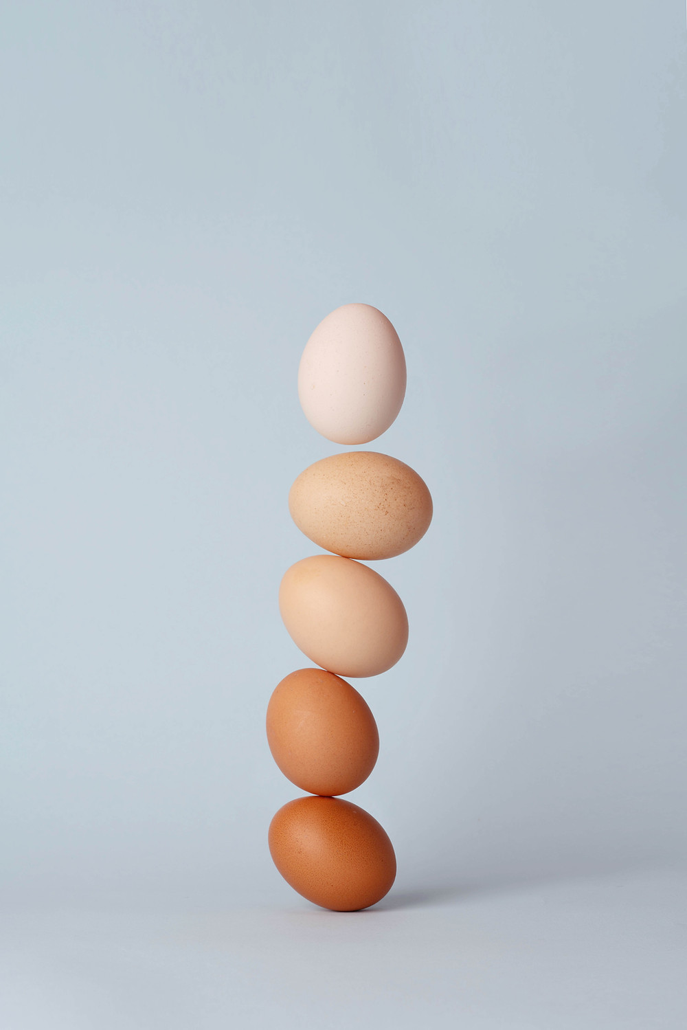 A tower of five eggs balancing precariously.