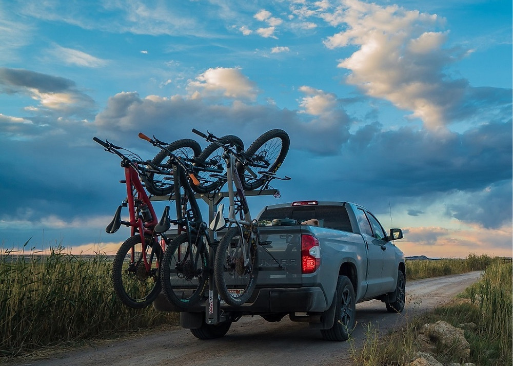 Image of VelociRAX bike racks carrying bikes on the back of a truck as the sun is setting