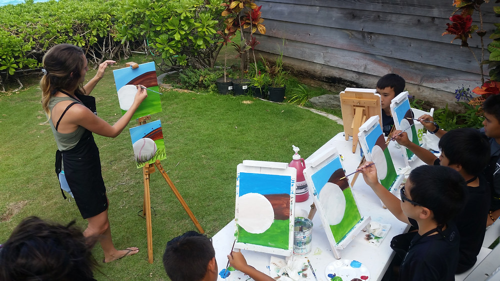 Cary and teammates learned to paint a baseball portrait on a beautiful afternoon in Lanikai