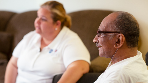 Caregiver aide laughs with patient at his home