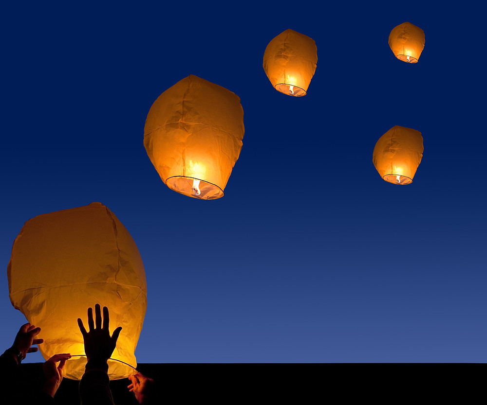paper lanterns floating in a night sky
