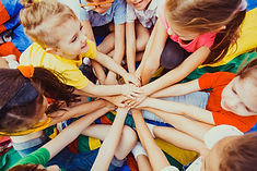 Group of children putting their hands to