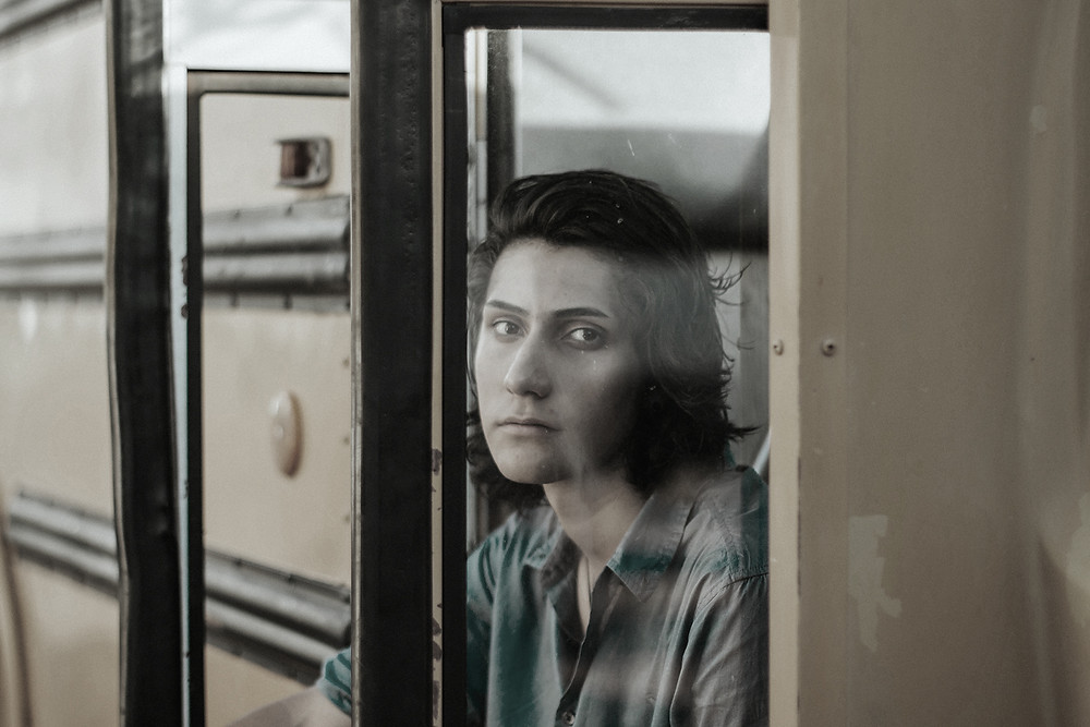 A high school student sitting in the entry of a bus.