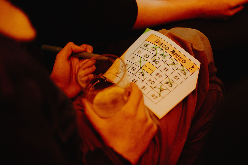 A disco bingo attendee ticking off numbers on their bingo sheet.