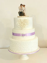 A stunning Wedding cake featuring wite on white with a touch of lilac, the perect cake for any wedding.