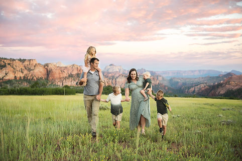 Tia Stout photo and her family walk through a field with mountains in the background
