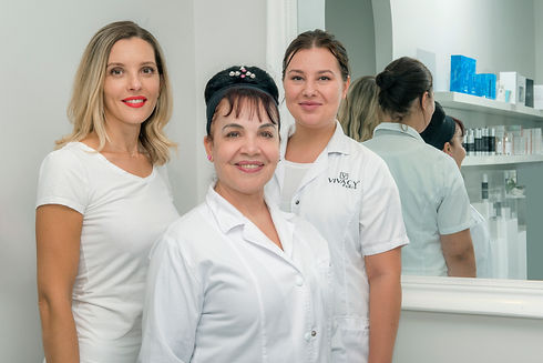 Dr Hala Mahfoud with two of her female clinicians standing behind either side of her. They are smiling and dressed in white, with a mirror behind them.