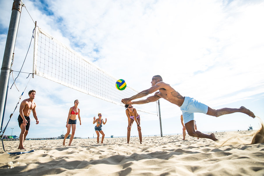 Group of friends playing beach volley -