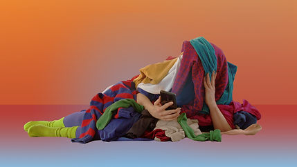 A figure covered in a pile of clothes lies on their side and looks at their phone. Their hands and feet poke out from the pile.