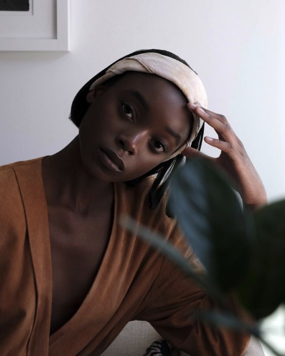 Black woman leaning her head on her hand