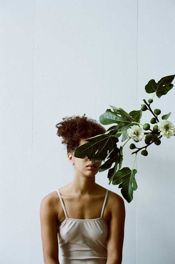 Woman sitting behind flowers and leaves covering her eyes.