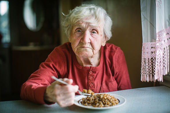 Elderly woman eats buckwheat porridge si
