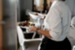 Tarjoilija kantaa ruoka-annoksia fine dining-ravintolassa Helsingissä.
