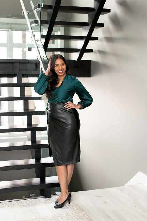 model standing by stairs with green wrap top and black leather skirt