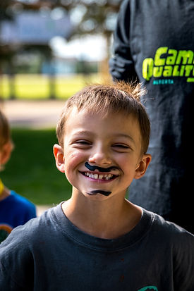 Smiling camper with a drawn on moustach and goatee