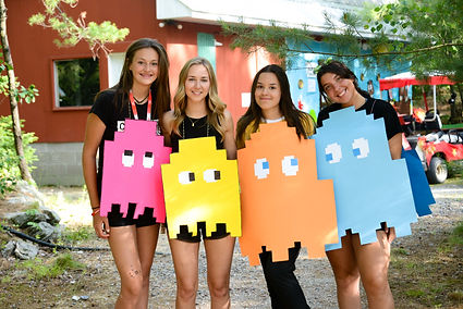 Four smiling teens at new heights wearing pacman ghost costumes
