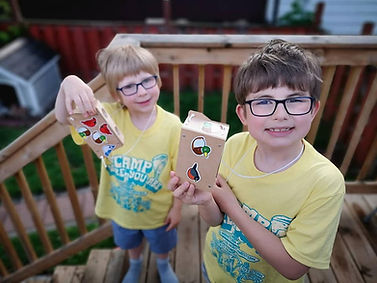 Two campers in Camp Where You Are t-shirts holding up a craft from Camp at Home