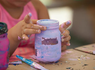 hands holding a painted jar