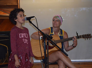 Camper singing into microphone and volunteer playing guitar