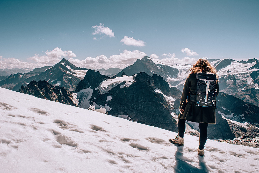 Girl standing in front of mountains with backpack