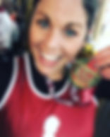 a girl holding a medal for running the St. Jude marathon