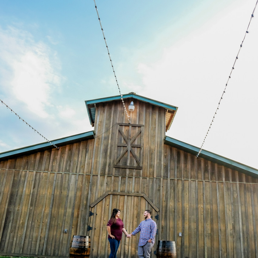 Engaged couple holding hands in front of the barn at Sowell Farms