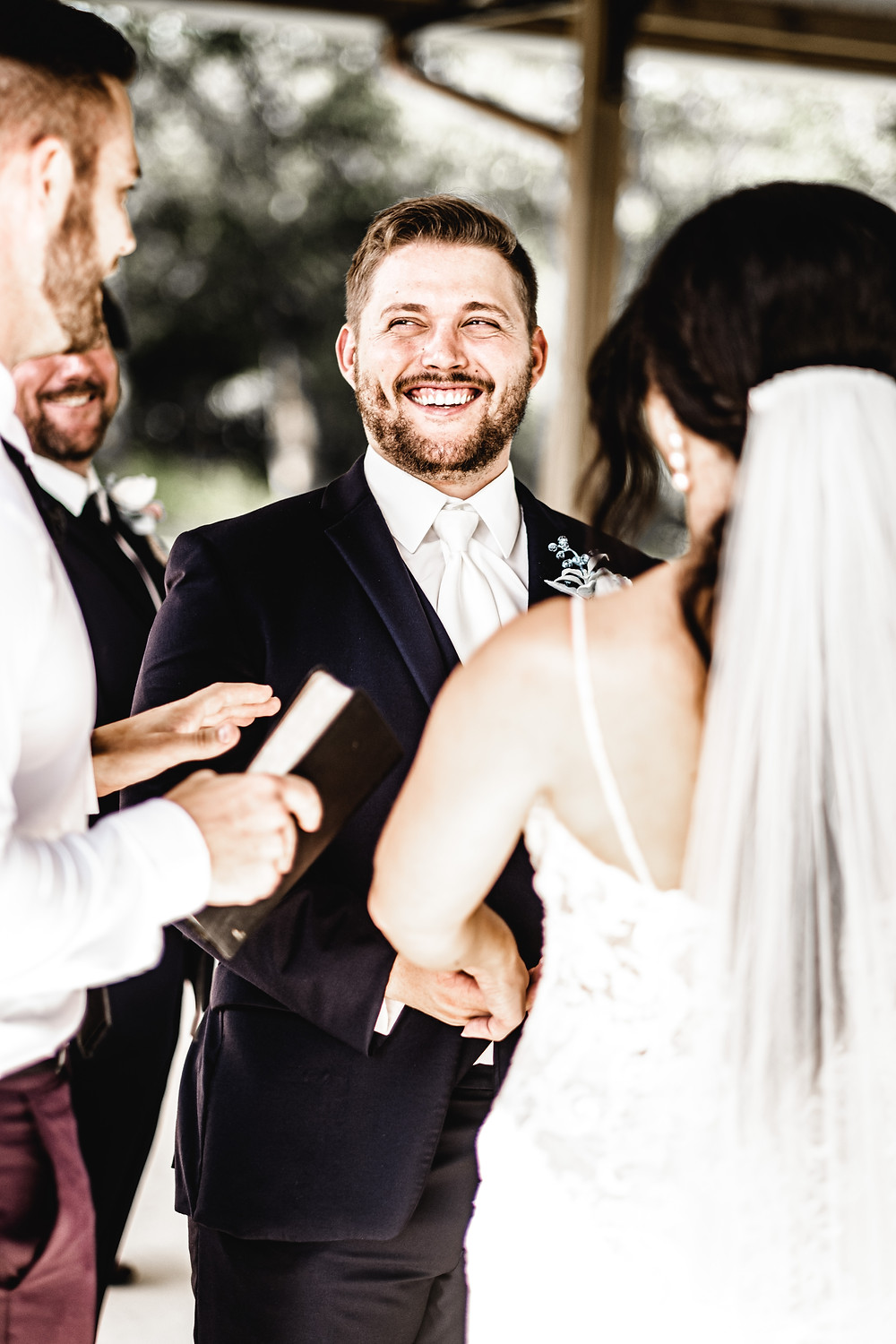 Groom laughing at altar during ceremony