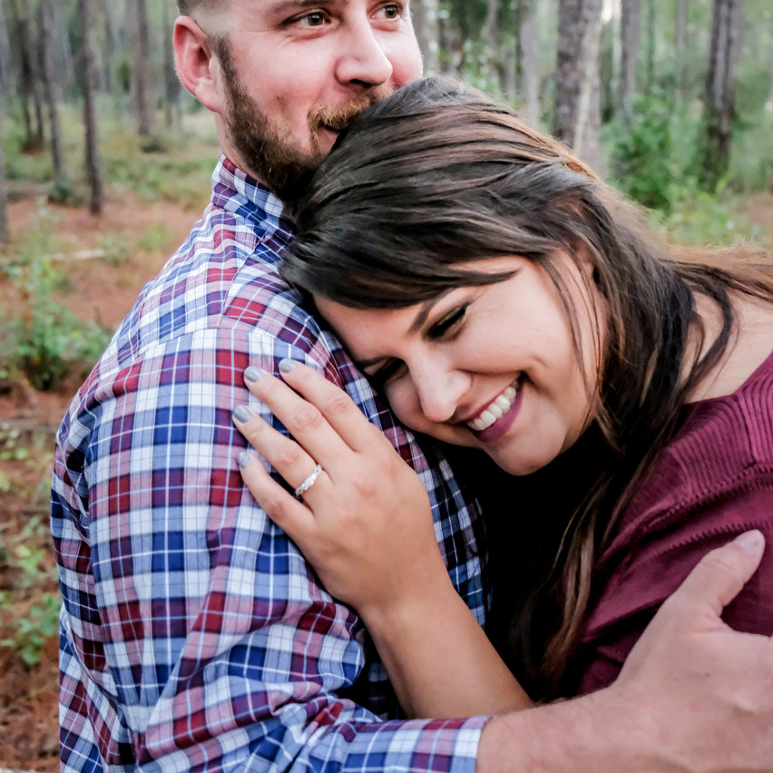 Engaged couple hugging in the woods
