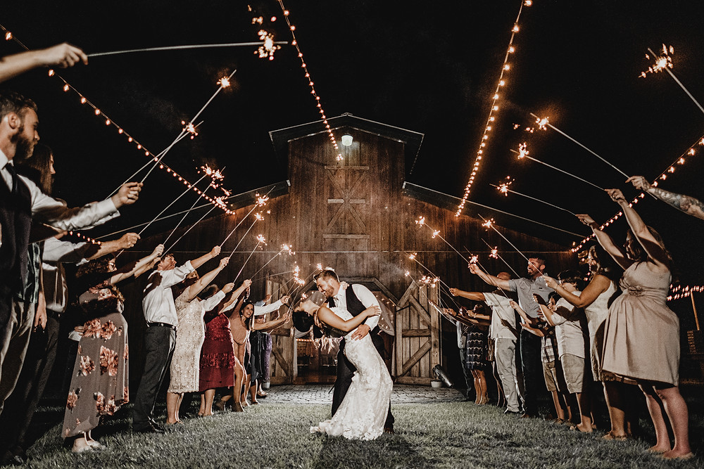 Groom dipping bride during sparkler exit at wedding