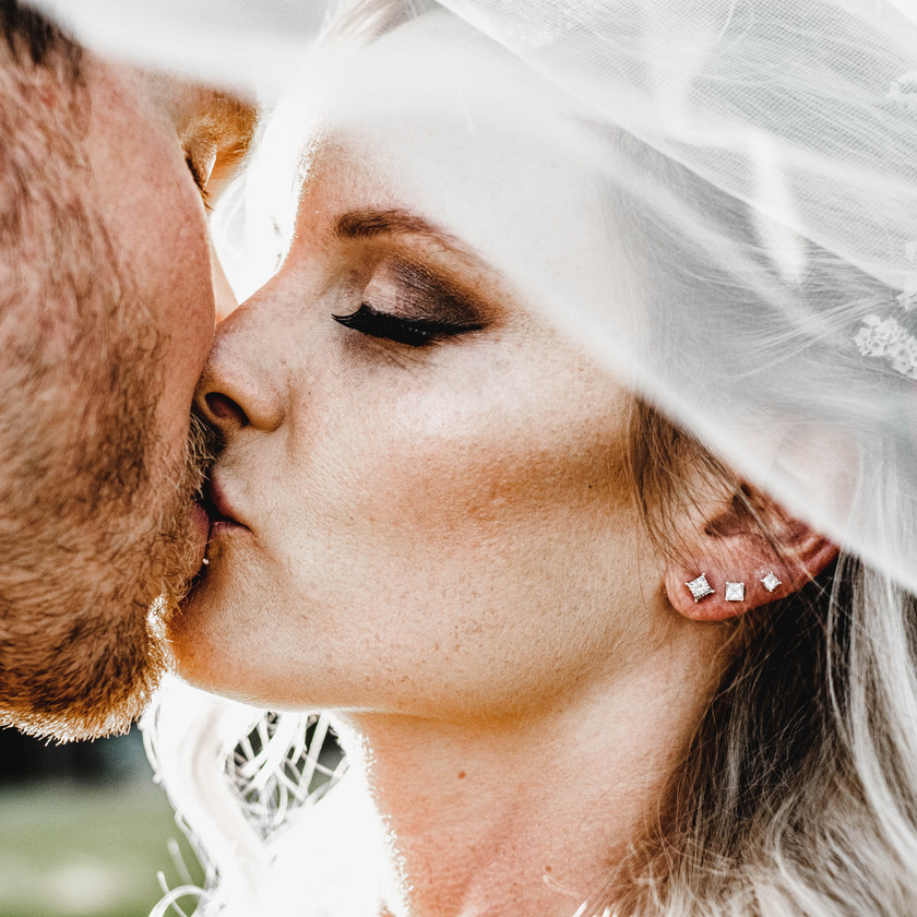 Bride and groom kiss under the veil