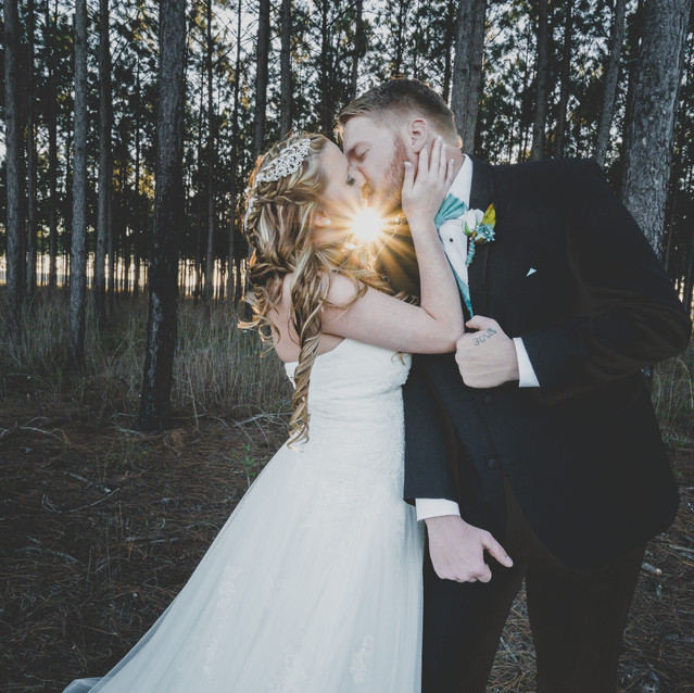 Newlyweds kissing in pine forrest