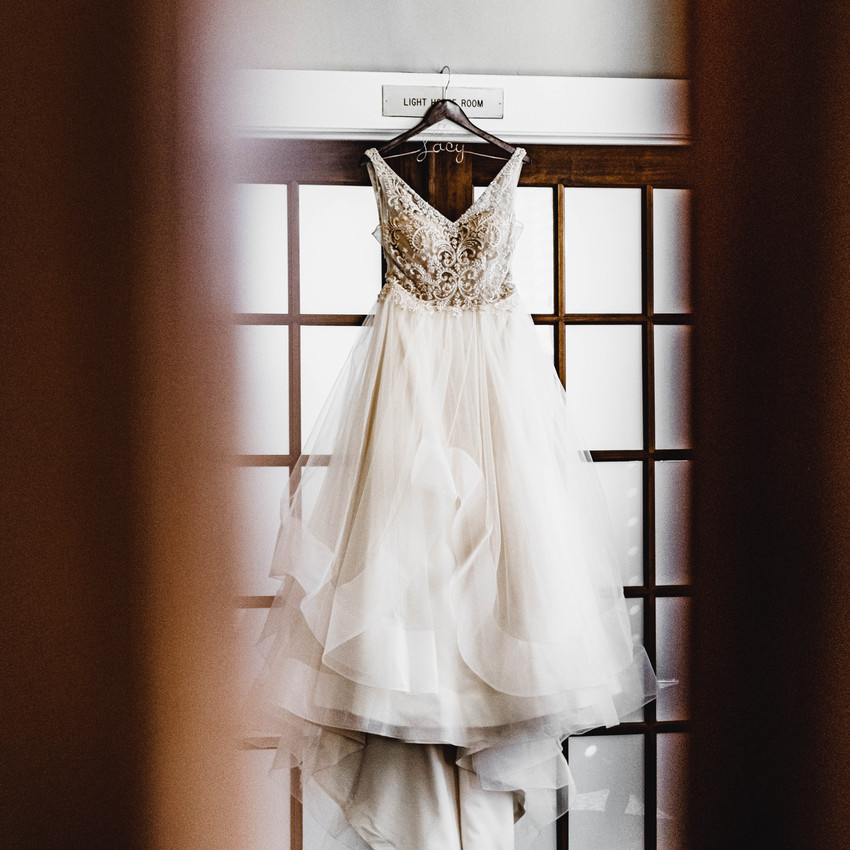 Beaded wedding dress hanging on door
