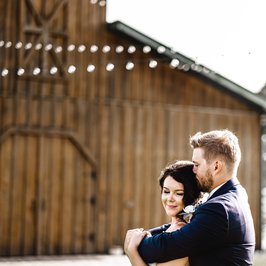 Groom kissing bride in front of barn
