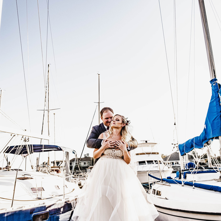 Groom holding his bride next to a few yachts