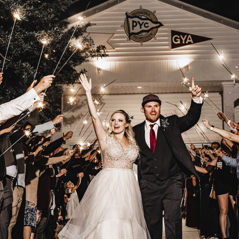 bride and groom celebrate while walking under sparklers