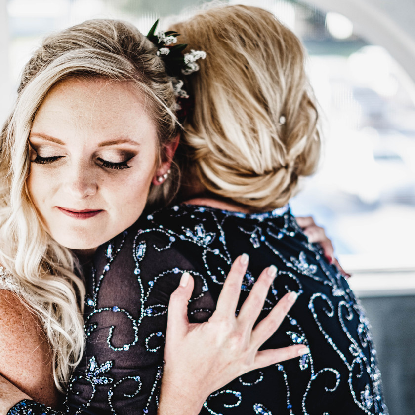 Mother of the bride hugging bride on the wedding day