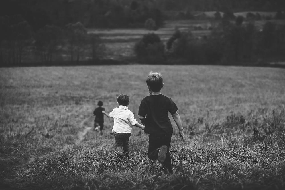 Crianças correndo no campo, imagem em preto e branco.