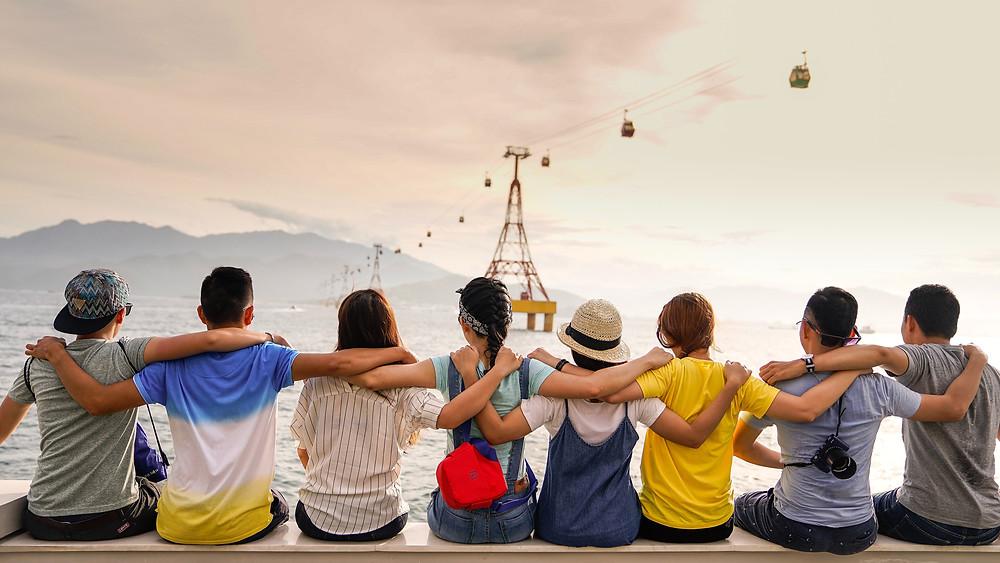 imagem de oito amigos abraçados de frente para o mar