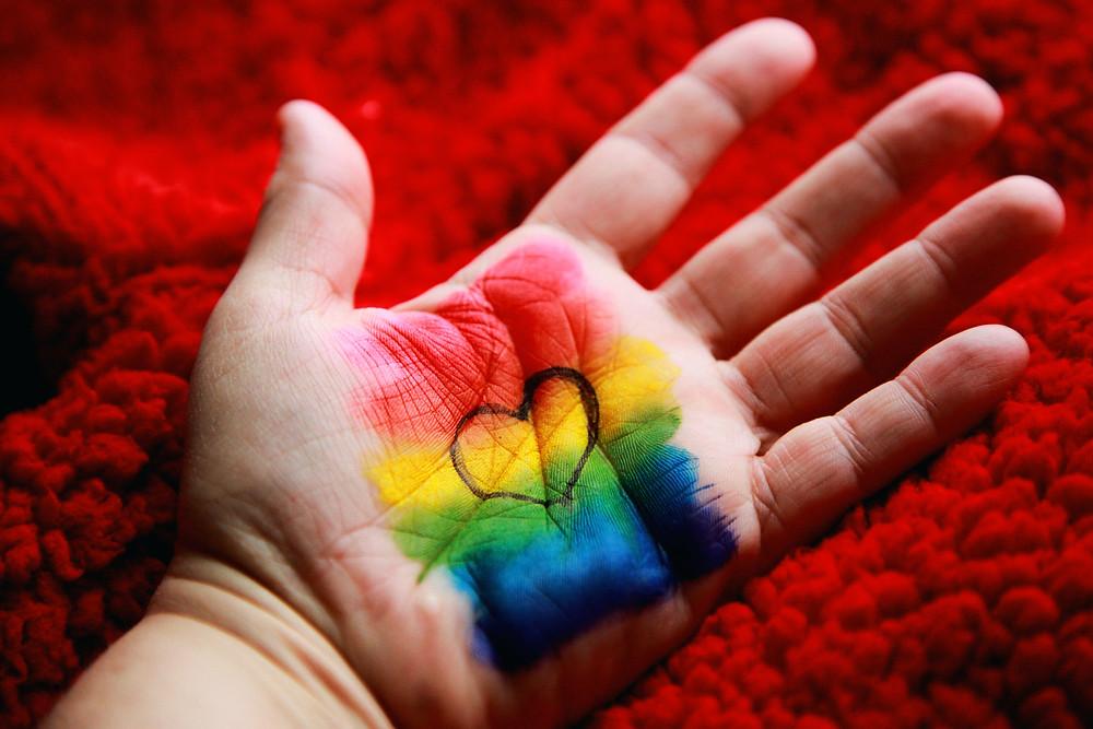 Dia do Orgulho LGBTQIAP+, palma da mão com as cores da bandeira LGBT e um coração no meio