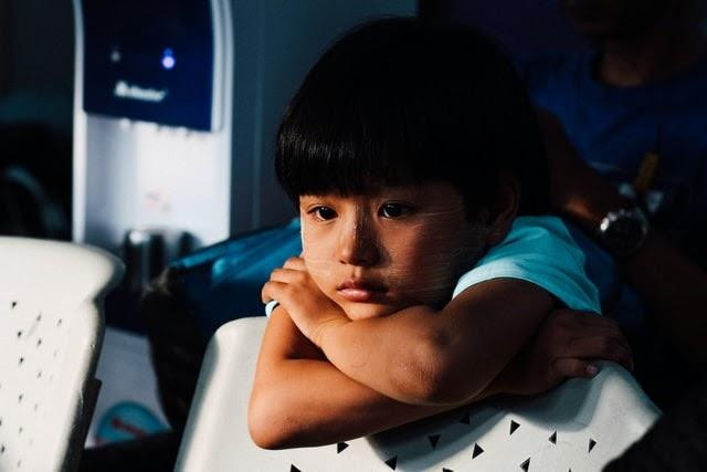 A sad child leaning over the back of a chair
