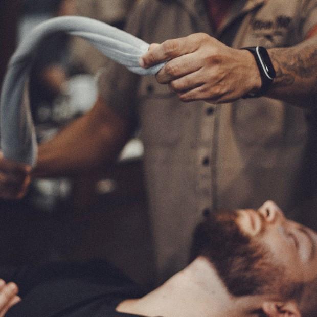 Colocar uma toalha aquecida no rosto antes de fazer a barba ajuda a abrir os poros (Foto: Divulgação/Barbearia Tarantino)
